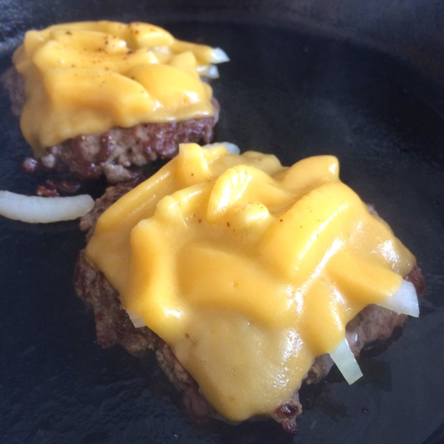 Seared burgers topped with onions and cheese